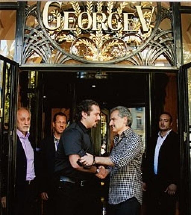 Al-Waleed bin Talal Saad Hariri welcoming at the entrance to the George V Hotel in Paris.