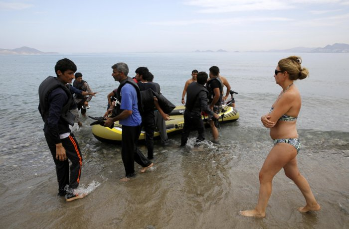 "A Spanish tourist watches Pakistani migrants arriving at a beach in the Greek island of Kos after paddling an engineless dinghy from the Turkish coast August 15, 2015. United Nations refugee agency (UNHCR) called on Greece to take control of the ""total chaos"" on Mediterranean islands, where thousands of migrants have landed. About 124,000 have arrived this year by sea, many via Turkey, according to Vincent Cochetel, UNHCR director for Europe. REUTERS/Yannis Behrakis"