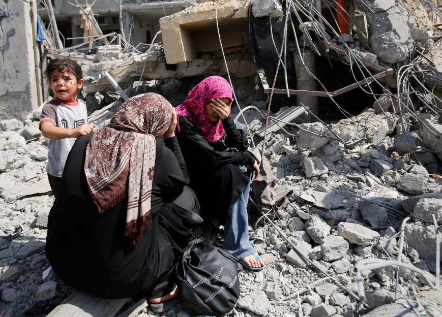 Palestinian women sit on the rubble of their home in Beit Hanoun, Gaza Strip, Friday, Aug. 1, 2014. A three-day Gaza cease-fire that began Friday quickly unraveled, with Israel and Hamas accusing each other of violating the truce. (AP Photo/Hatem Moussa)