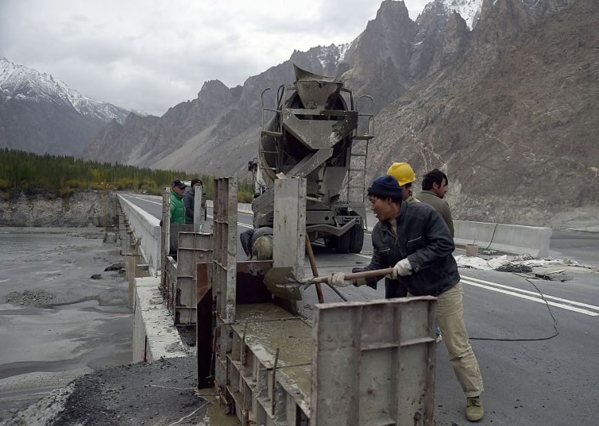 To go with story 'Pakistan-China-economy-transport, FEATURE' by Guillaume LAVALLÉE In this photograph taken on September 29, 2015, Chinese labourers work on the Karakoram highway, in Gulmit village of Hunza valley in northern Pakistan. A glossy highway and hundreds of lorries transporting Chinese workers by the thousands: the new Silk Road is under construction in northern Pakistan, but locals living on the border are yet to be convinced they will receive more from it than dust. AFP PHOTO / Aamir QURESHI (Photo credit should read AAMIR QURESHI/AFP/Getty Images)