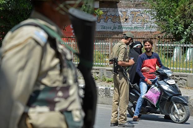 An Indian paramilitary trooper stops a Kashmiri couple during a twelfth day of curfew in downtown Srinagar on July 20, 2016. Residents in Indian-administered Kashmir are facing a shortage of food and critical medical supplies as the restive region continues to be under a security lockdown. Large parts of Indian-administered Kashmir have been under continuous 24-hour curfew since the death on July 8 of a popular rebel leader sparked wide-scale protests and clashes with government forces who have fired and killed 45 civilians so far. Around 3600 have been injured in the escalating unrest overwhelming the hospitals, officials said. / AFP / TAUSEEF MUSTAFA        (Photo credit should read TAUSEEF MUSTAFA/AFP/Getty Images)